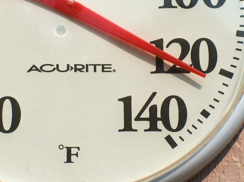 A thermometer showing 120 degrees Fahrenheit.